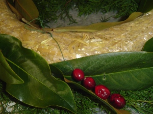 After securing floral wire to the back of the wreath, begin stringing fruit for the garland.