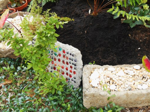 "An experimental ""stepping stone"" holds back the soil behind a second Azalea shrub, forming more border for the garden."