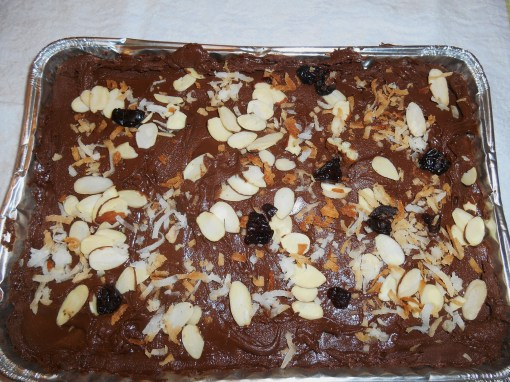 Pour the tempered chocolate into a shallow mold, and tip with more coconut, nuts, and chopped dried fruit.  This milk chocolate is ready to chill.